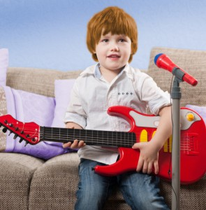 red-haired four-year-old playing electric guitar