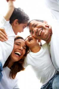 Latino/Hispanic family with pre-school children laughing & hugging each other