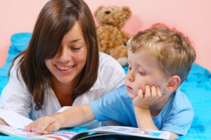 Young mother reads to her four-year-old son at bedtime.