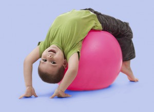 four-year-old boy having upside-down fun on an exercise ball