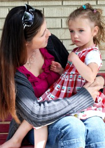 young mother chatting with slightly upset three-year-old outside pre-school
