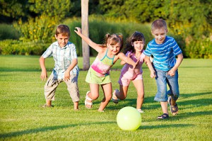 group of four pre-schoolers rave to kick a ball