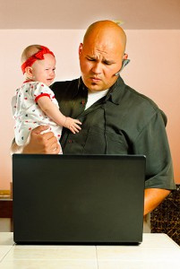 young father attempting to tend to infant daughter, computer and cell phone