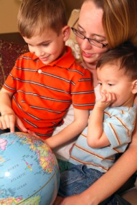young mother examines a globe with her two pre-school sons