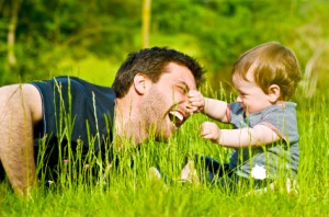 young father playing with toddler son in spring grass