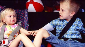toddler girl argues with four-year-old brother in back seat of car