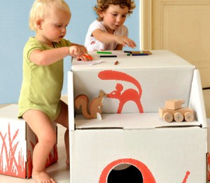 A Toddler and a three-year-old incorporate blocks and cardboard structures into their play.