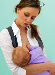 Young Caucasian mother in office attire breast-feeding her baby son