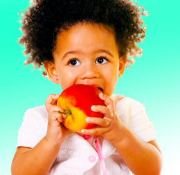 Three-year-old African-American girl begins to enjoy a very large peach.