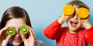 A brother and sister playfully cover their eyes with kiwi and orange slices