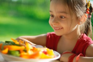 A four-year-old Hispanic/Latina girl eyes a plate of frech veggies at an outdoor eatery.