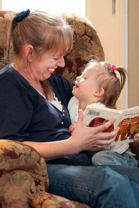Young grandmother and special needs toddler enjoy a book together