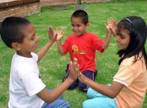Three Hispanic/Latino pre-schoolers enjoy an outside game of handclapping.