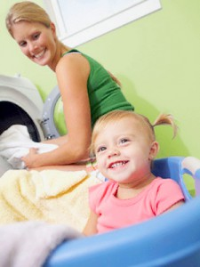 Toddler girl in laundry basket laughs as her mother empties a clothes dryer
