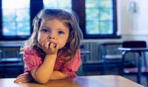 Confident four-year-old girl makes direct eye-contact with the viewer