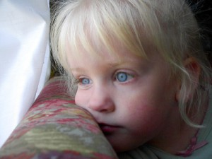 bored, blonde-haired, blue-eyed four-year-old looks wistfully out window
