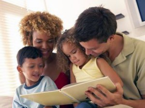 A young, mixed race family enjoys reading a book together.