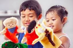 two shy, Asian pre-schoolers use puppets to tell stories
