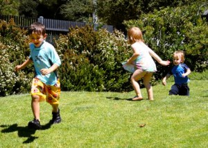 "Three pre-schoolers enjoy a game of ""tag"" outside on a sunny day."