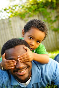 "Young African-American father and his three-year-old son play ""peek-a-boo"""