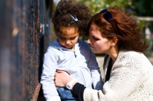 mother comforts four-year-old daughter on playground