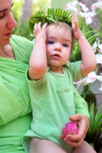 toddler with fern-leaf crown being gently held by his mother