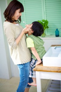 four-year-old Japanese boy gets his teeth brushed by his mother