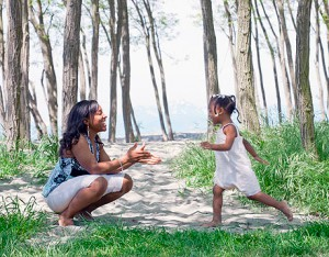 A three-year-old African American girl runs to her Mother's arms in a park