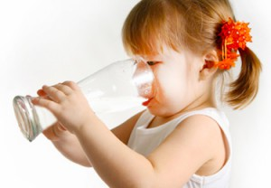 A toddler girl in the midst of drinking a large glas of milk.