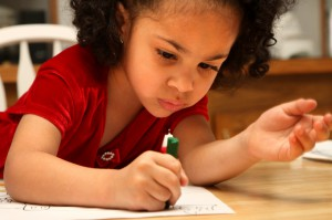 four-year-old african american girl concentrating on her drawing
